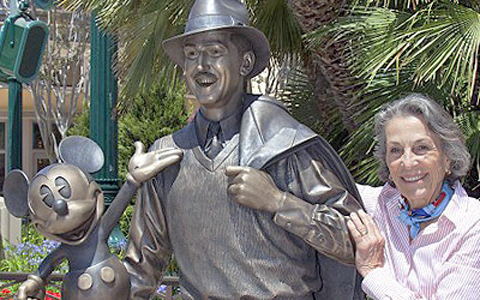 Diane Disney by Statue of Walt Disney and Mickey