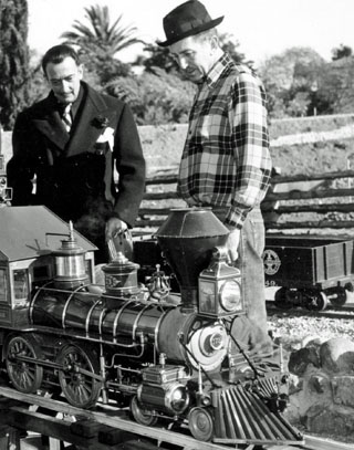 Walt Disney showing off his backyard train set to Salvadore Dali