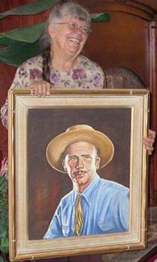 Kathi Hilton with a portrait of her dad, artist John W. Hilton